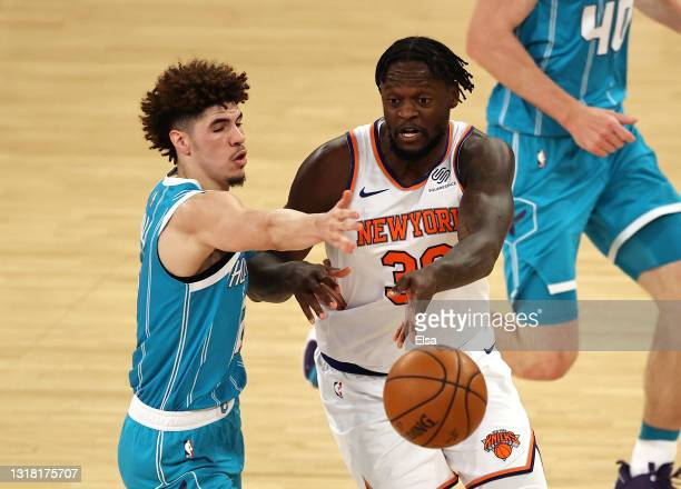 Julius Randle of the New York Knicks passes under pressure from LaMelo Ball of the Charlotte Hornets in the second quarter at Madison Square Garden...