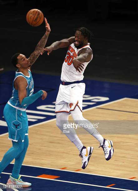 Julius Randle of the New York Knicks sends the ball to teammate Alec Burks as P.J. Washington of the Charlotte Hornets defends in overtime at Madison...