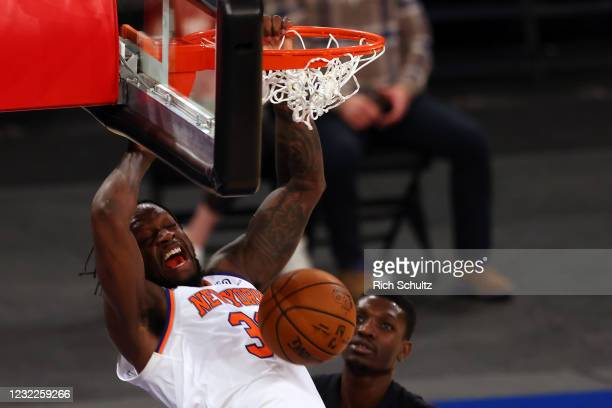 Julius Randle the New York Knicks dunks as Chris Boucher of the Toronto Raptors looks on at Madison Square Garden on April 11, 2021 in New York City....