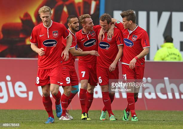 Julius Reinhardt of Heidenheim jubilates with team mates after scoring the first goal during the third league match between FC Hansa Rostock and 1FC...