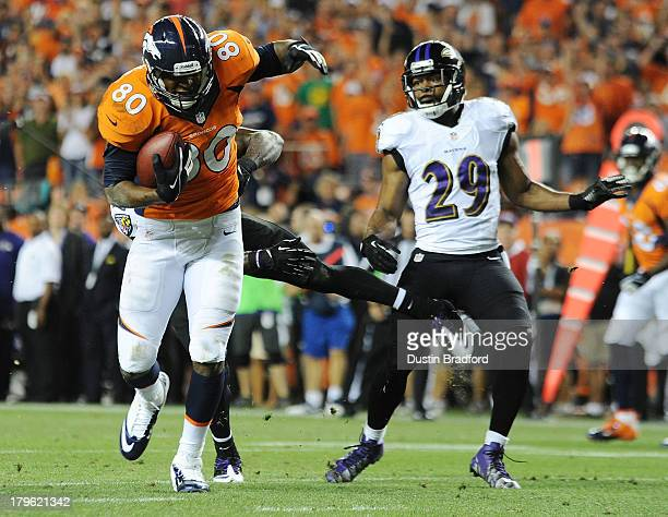 Julius Thomas of the Denver Broncos runs by Michael Huff of the Baltimore Ravens before running into the end zone for a touchdown in the second...