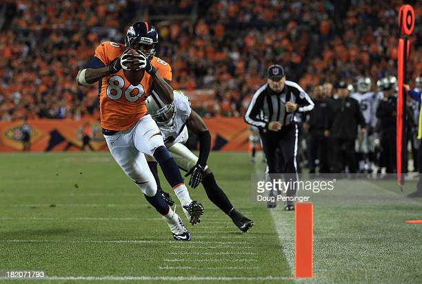 Julius Thomas of the Denver Broncos sheds Kevin Burnett of the Oakland Raiders for a touchdown reception at Sports Authority Field at Mile High on...
