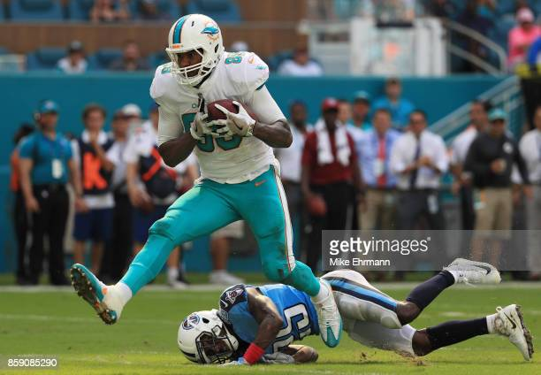 Julius Thomas of the Miami Dolphins tries to avoid the tackle of Adoree' Jackson of the Tennessee Titans in the fourth quarter on October 8 2017 at...