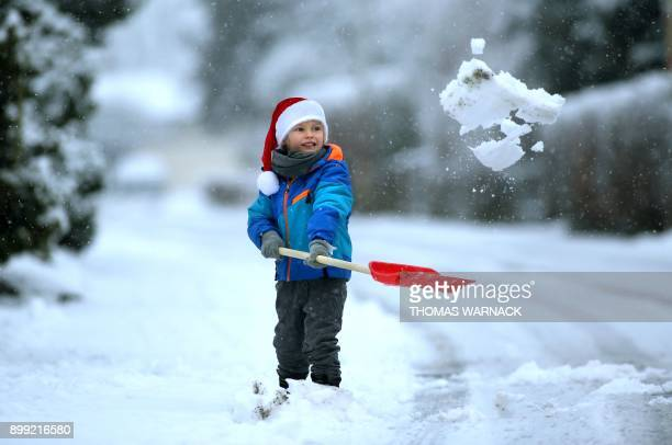 Julius Xaver shovels snow in Riedlingen southern Germany on December 28 2017 / AFP PHOTO / dpa / Thomas Warnack / Germany OUT