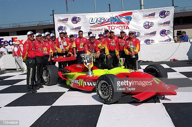 Driver Tony Kanaan poses with his team and car after winning the US 500 part of the 1999 CART FedEx Championship Series at the Michigan International...