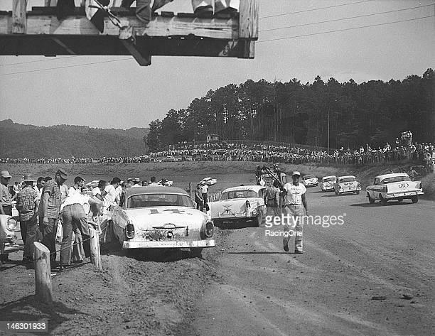 Track crews work on removing the cars of Billy Myers and Brownie King from the dirt berm after they tangled during the NASCAR Cup race at...