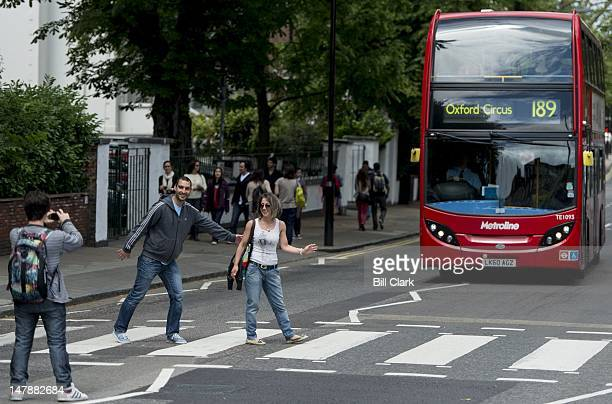 Tourists pose for photos on the iconic crosswalk on Abbey Road in London on Sunday July 1 2012 Mobs of tourists often delay traffic at the crosswalk...