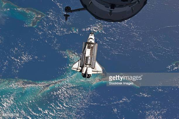 July 10, 2011 - Space Shuttle Atlantis over the Bahamas. Part of a Russian Progress spacecraft is visible in the foreground.