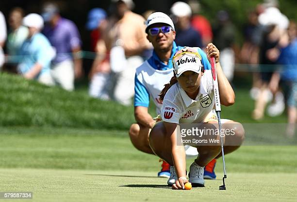 Mi Hyang Lee sets the ball on the 6th green as Ivan Galdame her caddie helps line up her shot during the second round of the US Women's Open at...
