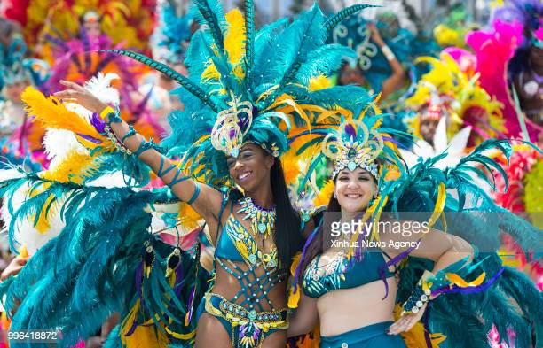 Revellers pose for photos during the official launch ceremony of the 2018 Toronto Caribbean Carnival at Nathan Philips Square in Toronto Canada July...