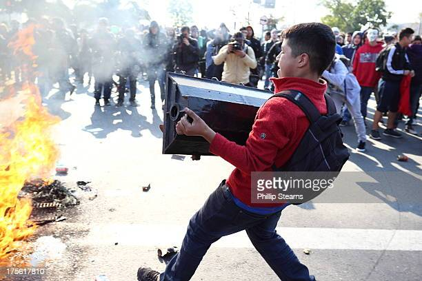 CONTENT] July 11 2013 Protest March and Demonstration Santiago Chile Julio 11 A young protester throws a traffic light into a fire burning in the...
