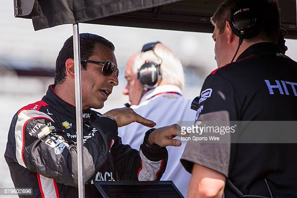 Indy Car Driver Helio Castroneves takes debriefs with his team during practice 2 leading up to the running of the ABC Supply Wisconsin 250 at The...