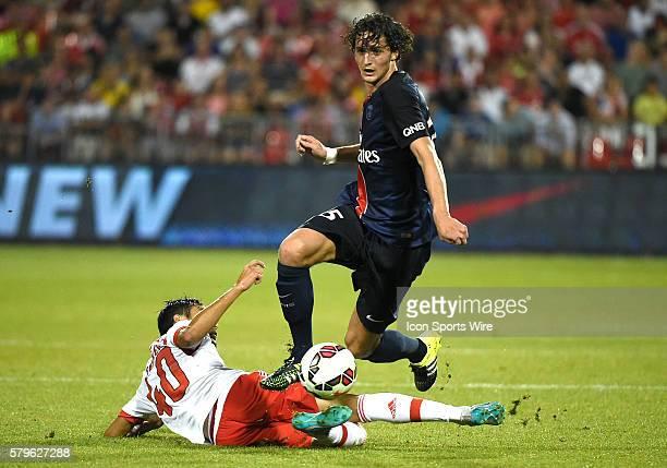 Paris St. Germain midfielder Adrien Rabiot hurdles a sliding tackle from Benfica midfielder Joao Teixeira in the second half of an International...