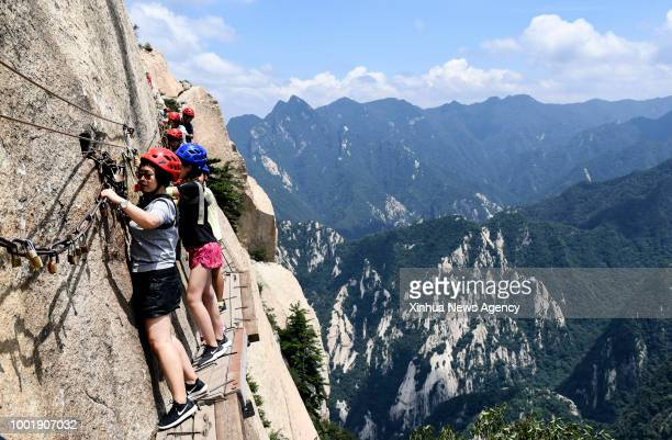 Tourists navigate Chang Kong Plank Road at Huashan Mountain in Huayin City northwest China's Shaanxi Province July 18 2018 Built clinging to the...