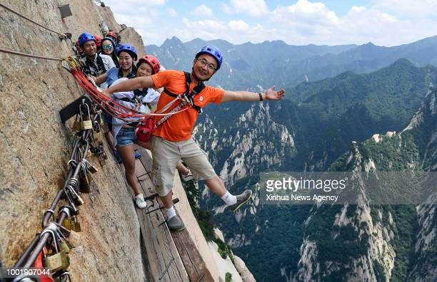 Tourists pose for photos on Chang Kong Plank Road at Huashan Mountain in Huayin City northwest China's Shaanxi Province July 18 2018 Built clinging...