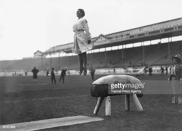 A danish gymnast performing a perfect dismount from a pommel horse during the 1908 London Olympics