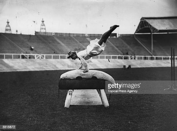 A Danish gymnast performing on a gymnastic pommel horse at the 1908 London Olympics