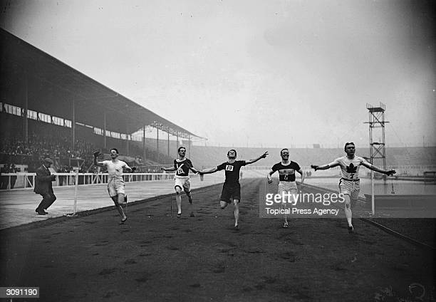 Robert Kerr of Canada wins the final of the 100 yards race at the British Amateur Athletic Association Championships in London with Reginald Walker...