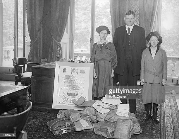 American Statesman Herbert Hoover closely associated with relief of distress in Europe he is standing with his wife and daughter by a poster...