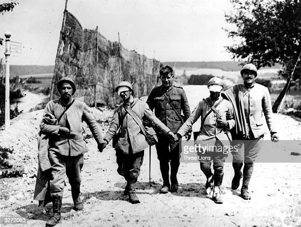 Gassed and blinded French infantrymen are led by comrades and escorted by British soldiers from the second Battle of the Marne