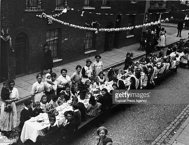 A London street party on Peace Day July 1919 A long trestle table has been set up with food and paper chains decorate the street
