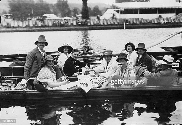 Visitors to the Henley Regatta join in the watery fun by having a picnic luncheon in adjoining rowing boats on the first day of the Regatta