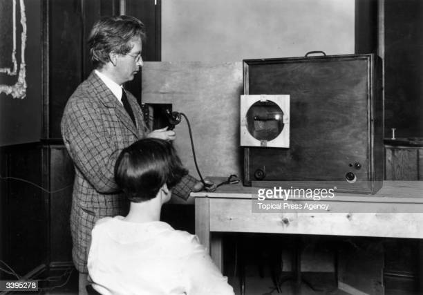 Scottish electrical engineer and television pioneer John Logie Baird with his 'televisor' The round screen on the front of the cabinet shows an...