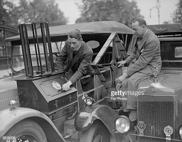 The controls of a 'car radio' which looks like a piece of furniture strapped to the outside of the bonnet are being adjusted A large diamond shaped...