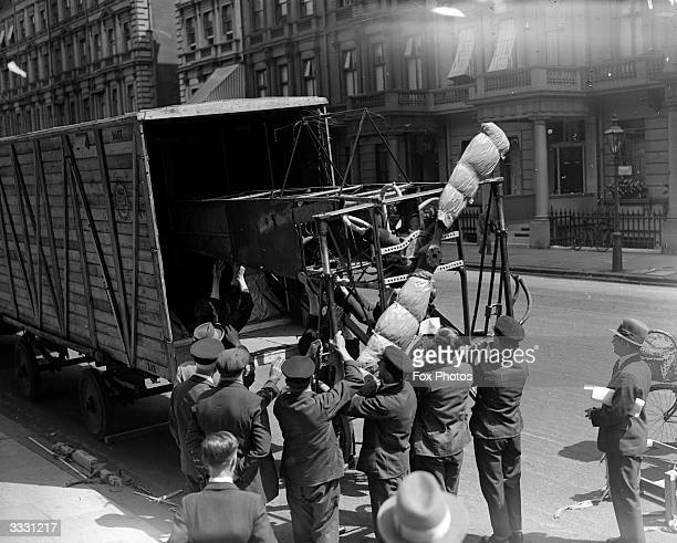 A monoplane designed by Louis Bleriot being unloaded from a lorry outside the Science Museum London