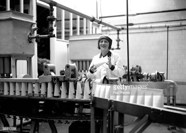 A woman holding one of the new cardboard milk cartons as a continuous line of them pass by on a conveyor belt at a milk bottling plant