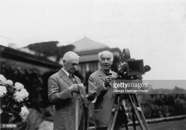 American inventor and industrialist George Eastman founder of the Eastman Kodak Company examines a strip of film and American inventor Thomas Edison...