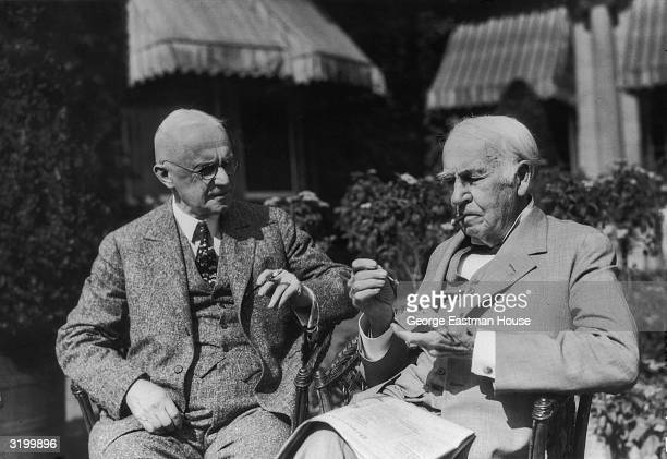 American inventors Thomas Edison and George Eastman founder of the Eastman Kodak Company smoke while sitting in wicker chairs in the yard at Eastman...