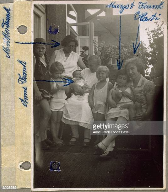 EXCLUSIVE A photo from Anne Frank's photo album of Anne Frank held by a woman being welcomed by her sister Margot's friends on a balcony with names...