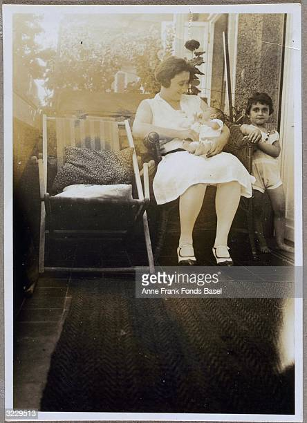 EXCLUSIVE Edith FrankHollander holding infant daughter Anne Frank on her lap with daughter Margot Frank standing next to them on a balcony Marbachweg...