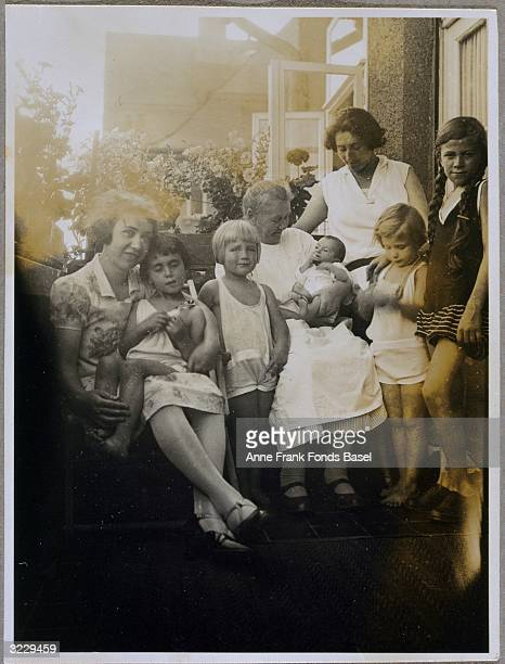 EXCLUSIVE Newborn Anne Frank held by an elderly woman being welcomed by her sister Margot's friends on a balcony Marbachweg Frankfurt am Main Germany...