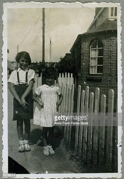 EXCLUSIVE A fulllength portrait of Anne Frank and her sister Margot Frank standing on a sidewalk next to a fence From Anne Frank's photo album