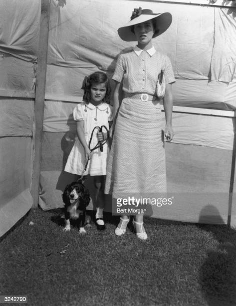 EXCLUSIVE Fulllength portrait of Jacqueline Bouvier standing beside her mother Mrs John V Bouvier III while holding her dog 'Bonnett' by its leash at...