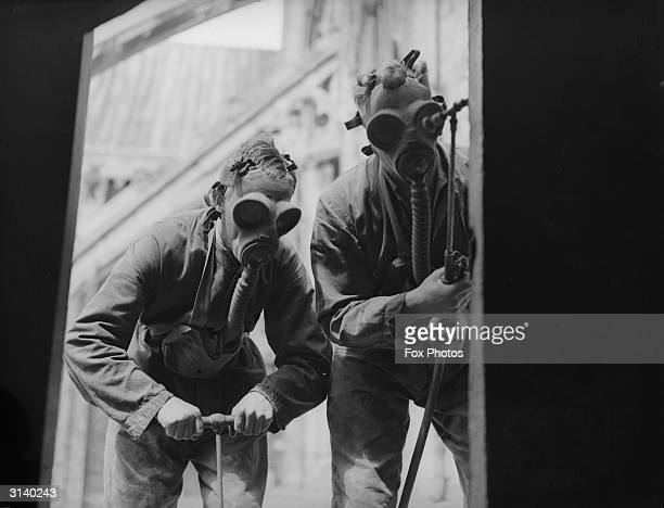Pest control men in gas masks spray insecticide around Winchester Cathedral in an attempt to exterminate an infestation of death watch beetles