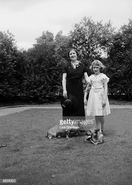 Elizabeth, Duchess of York with Princess Elizabeth and their corgi dogs in the grounds of their London home, 145 Piccadilly.
