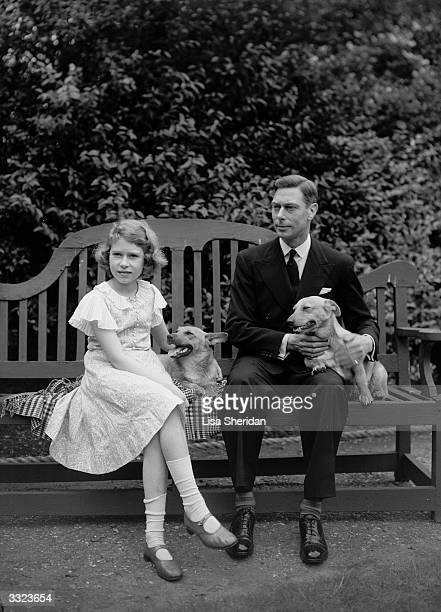 George Duke of York and Princess Elizabeth sitting on a bench with their corgi dogs in the grounds of their London home 145 Piccadilly