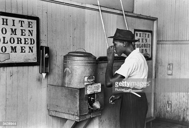 An African-American man drinking at a segregated drinking fountain in Oklahoma City, Oklahoma.