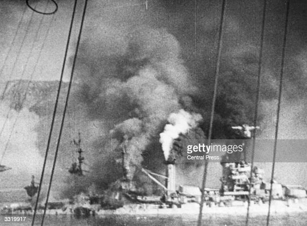 The French warship Bretagne partly submerged and enveloped in dense smoke after being attacked by British warships to prevent her from falling into...