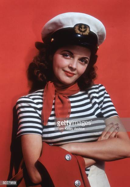 Actress Juanita Stark poses for the cover of 'Coronet' magazine in a black and white striped shirt a red bandanna and a sailor's cap holding a red...