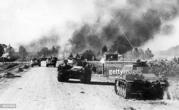 Panzer units of the German Army pass through a blazing Russian village torched by the evacuees on their oneway journey to the battlefront