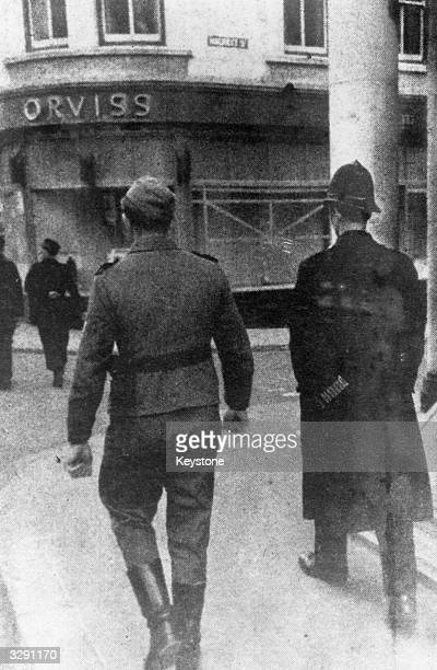 British policeman and German soldier patrol the streets of St Helier, Jersey, together during the German occupation of the Channel Islands.