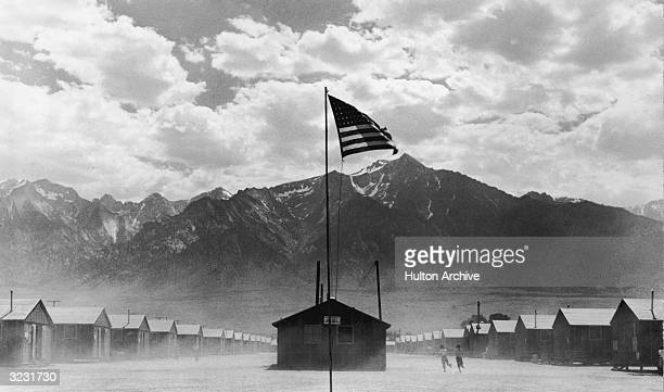 A US flag flies at a JapaneseAmerican internment camp which is surrounded by mountains in Manzanar California World War II