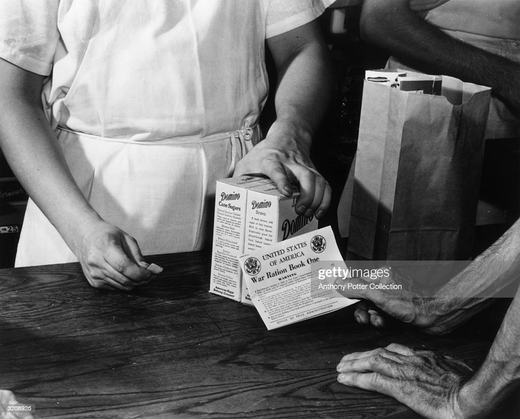 Close-up of a man behind a counter handing over two boxes of Domino sugar to a man handing over a War Ration Book. In an effort to ration sugar, coupons from the War Ration Books assured a just distribution of the nation's sugar supply to all.