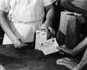 July 1942 closeup of a man behind a counter handing over two boxes of picture id3208925?s=170x170