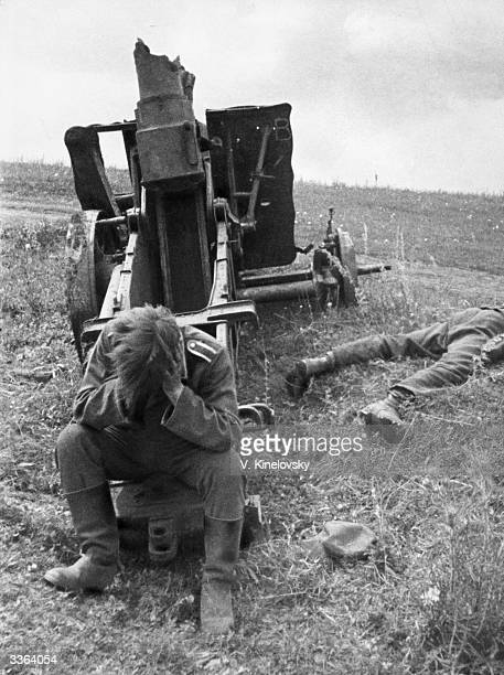 A German soldier sitting with his head in his hands by a destroyed heavy artillery gun and the corpse of one of his compatriots during the Kursk...