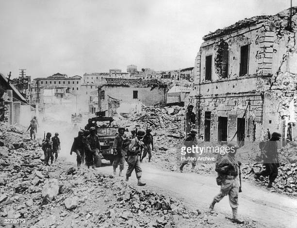 French troops of the 5th Army advance through the ruined streets of Portoferraic on the island of Elba.